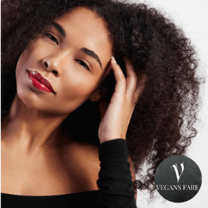 black owned vegan hair care, black woman with afro hair style tussling hair with hand wearing red lipstick