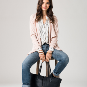 vegan woman sat ona stool holding a black vegan leather handbag, vegan clothing brands