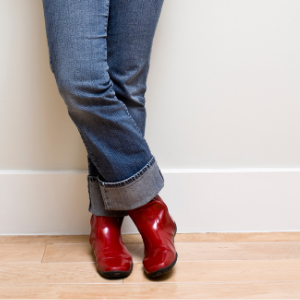 denim jeans legs wearing red shiny vegan boots, vegan shoes and footwear